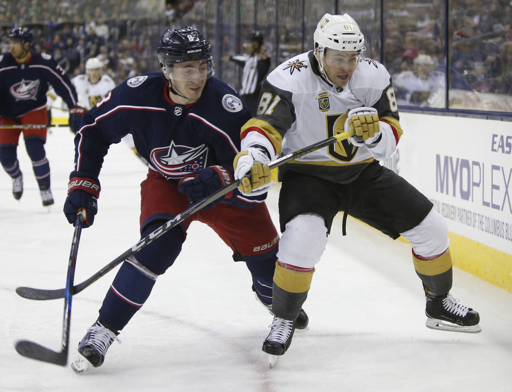 Columbus Blue Jackets' Zach Werenski, left, and Las Vegas Golden Knights' Jonathan Marchessault fight for position during the first period of an NHL hockey game Tuesday, March 6, 2018, in Columbus ...