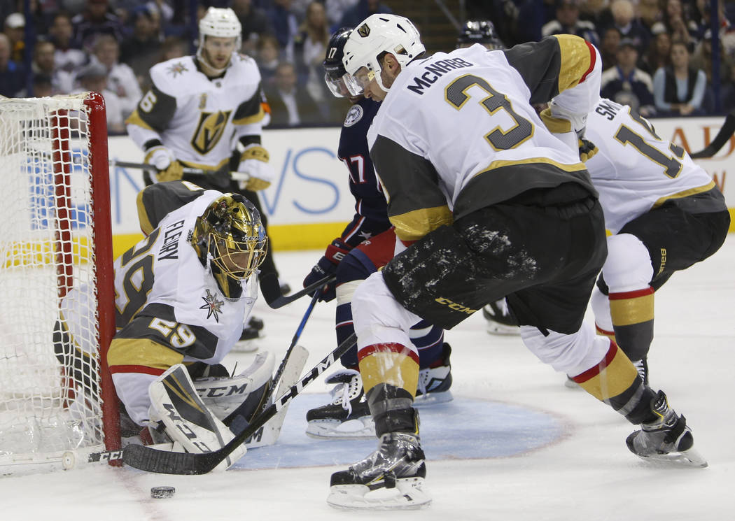 Las Vegas Golden Knights' Marc-Andre Fleury, left, makes a save as teammate Brayden McNabb, right, and Columbus Blue Jackets' Brandon Dubinsky look for a rebound during the second period of an NHL ...