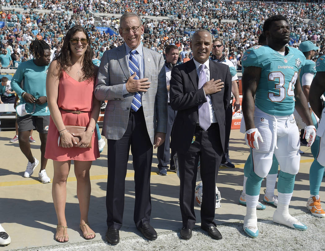 In this Sept. 20, 2015, file photo, Miami Dolphins owner Stephen M. Ross, second from left, stands on the sideline during the national anthem before an NFL football game against the Jacksonville J ...