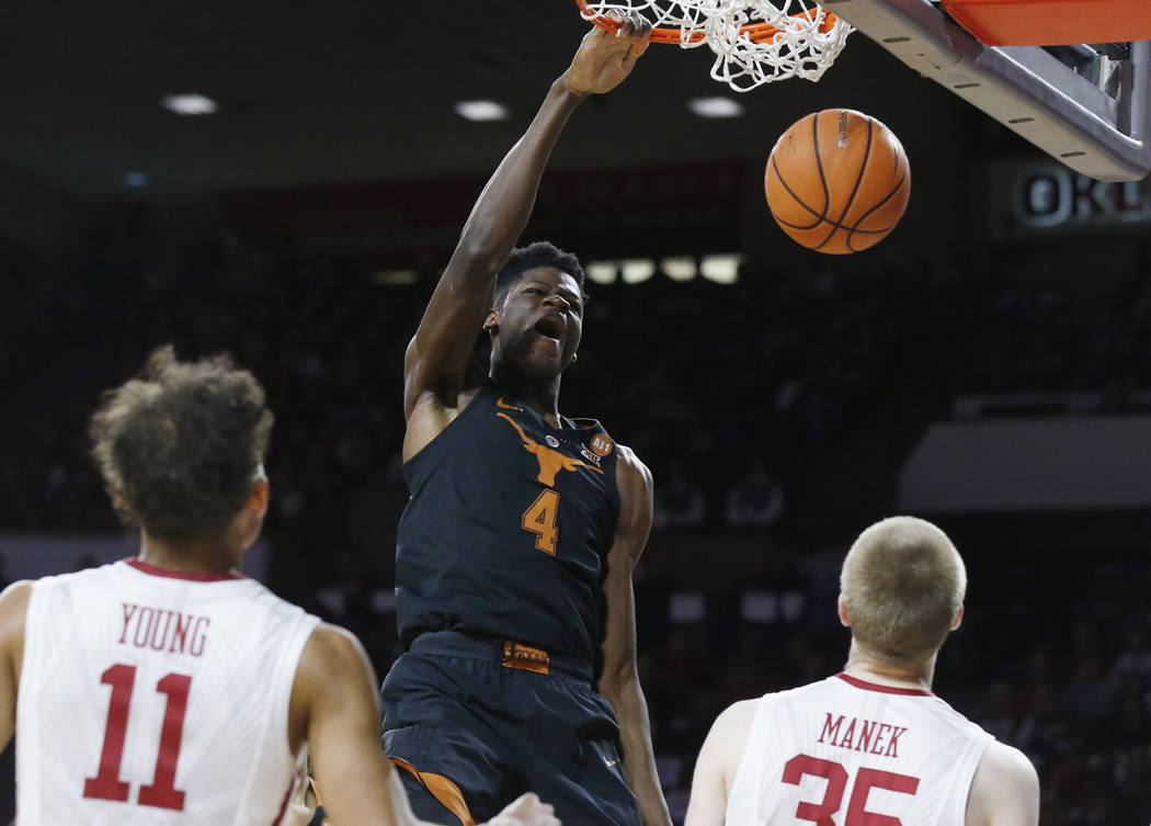In this Feb. 17, 2018, file photo, Texas forward Mohamed Bamba (4) dunks in front of Oklahoma guard Trae Young (11) and forward Brady Manek (35) in the first half of an NCAA college basketball gam ...