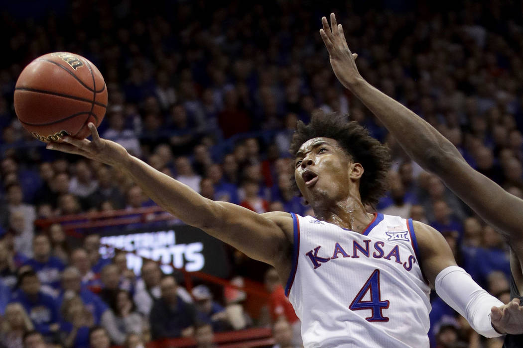 In this Jan. 2, 2018, file photo, Kansas' Devonte' Graham puts up a shot during the first half of an NCAA college basketball game against Texas Tech, in Lawrence, Kan. (AP Photo/Charlie Riedel, File)