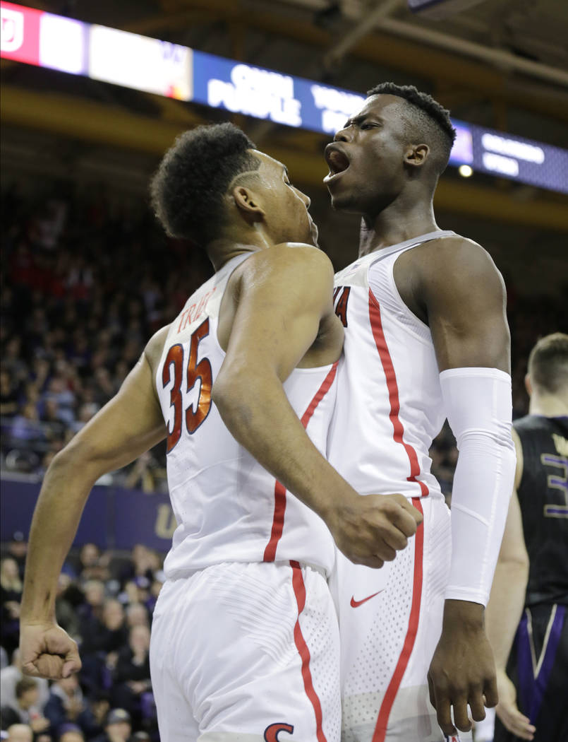 Arizona's Allonzo Trier, left, and Deandre Ayton chest bump after a play against Washington during the second half of an NCAA college basketball game Saturday, Feb. 3, 2018, in Seattle. Washington ...