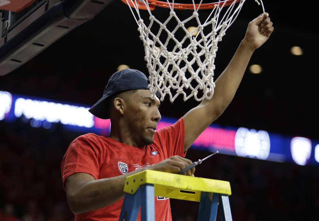 Arizona guard Allonzo Trier (35) cuts down the net after winning the Pac-12 title after an NCAA college basketball game against California, Saturday, March 3, 2018, in Tucson, Ariz. Arizona defeat ...