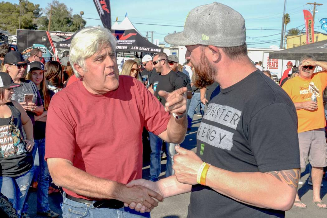 "Jay Leno, left, stops to talk to off-road racing champion BJ Baldwin as the Mint 400 off-road vehicles parade down Fremont Street in Las Vegas to their ""tech"" inspections for the big race on Satur ..."