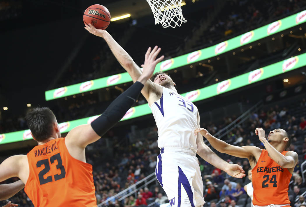 Washington Huskies forward Sam Timmins (33) goes to the basket between Oregon State Beavers center Gligorije Rakocevic (23) and guard Kendal Manuel (24) during the Pac-12 basketball tournament at  ...