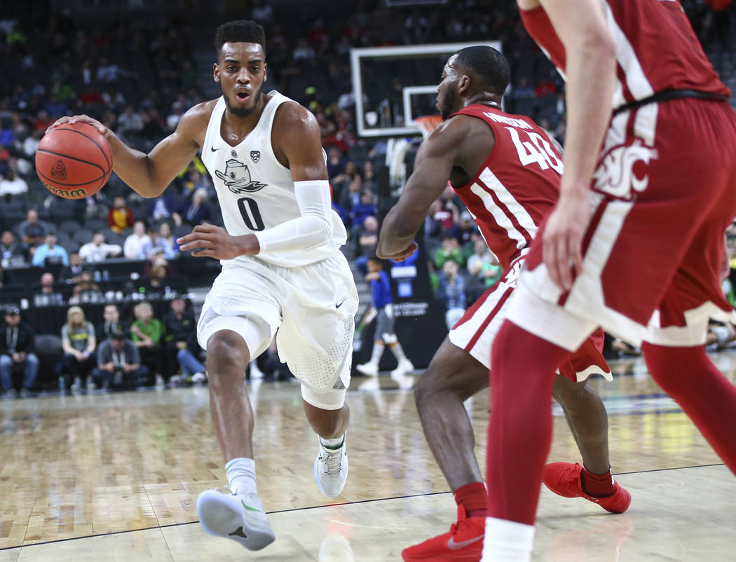 Oregon Ducks forward Troy Brown (0) drives past Washington State Cougars guard Kwinton Hinson (40) during the Pac-12 basketball tournament at T-Mobile Arena in Las Vegas on Wednesday, March 7, 201 ...