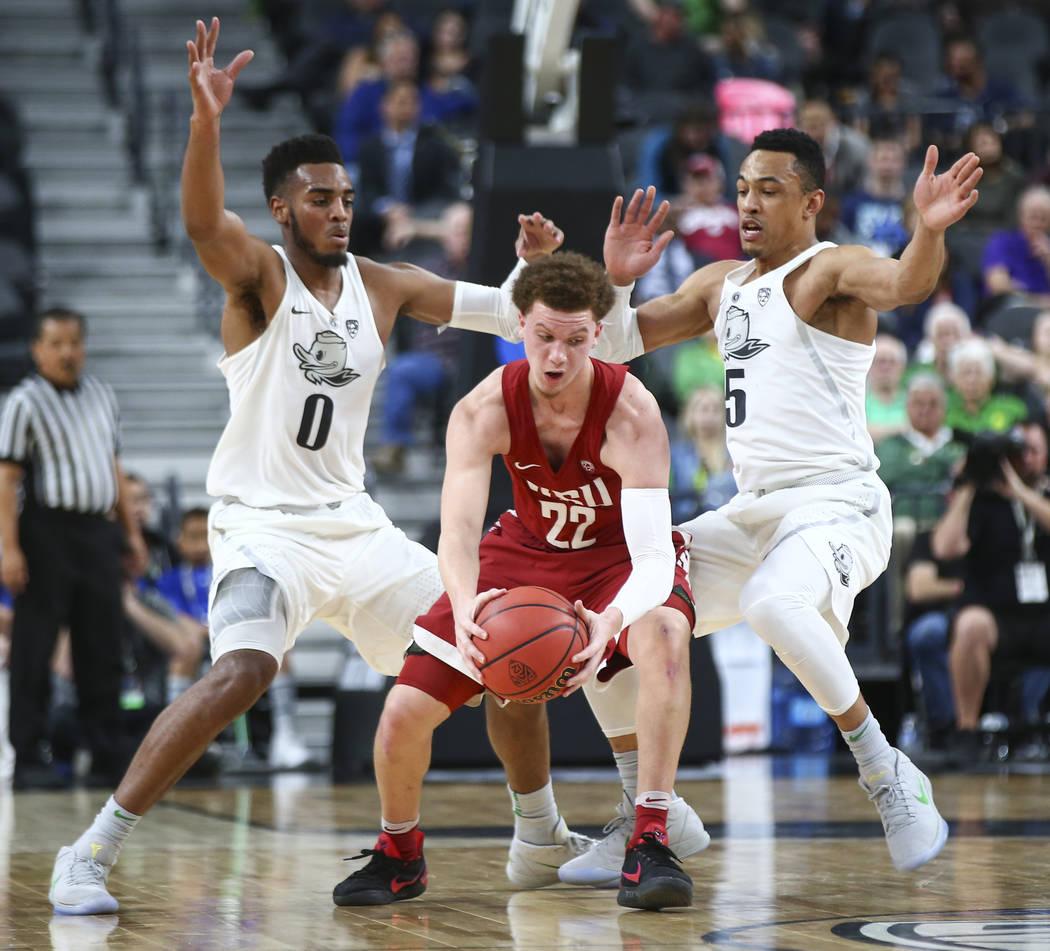 Washington State Cougars guard Malachi Flynn (22) looks to get around Oregon Ducks forward Troy Brown (0) and Oregon Ducks guard Elijah Brown (5) during the Pac-12 basketball tournament at T-Mobil ...