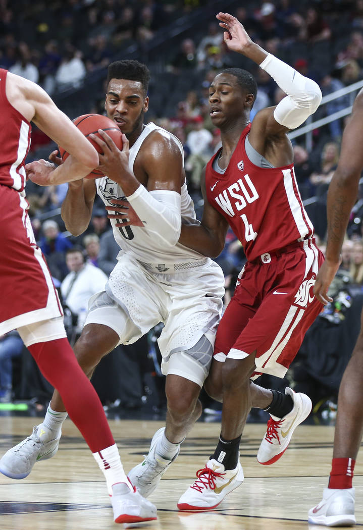 Oregon Ducks forward Troy Brown (0) drives against Washington State Cougars guard Viont'e Daniels (4) during the Pac-12 basketball tournament at T-Mobile Arena in Las Vegas on Wednesday, March 7,  ...