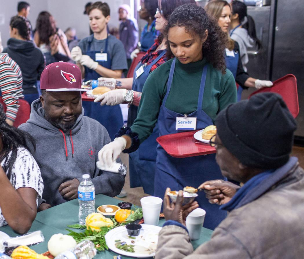 Volunteer Lehua Kanehe, 14, of Las Vegas, center, serves a free Thanksgiving meal to Lee Clark, 39, of Las Vegas, left, at Catholic Charities of Southern Nevada in Las Vegas, Thursday, Nov. 23, 20 ...
