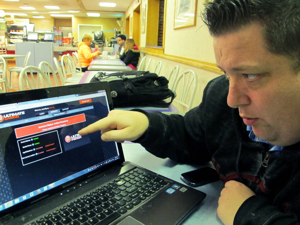 Joseph Brennen tries to log on to a gambling site while at a highway rest stop in Egg Harbor Township N.J., on the first night of New Jersey's Internet gambling test, Nov. 21, 2013. On Thursday, J ...