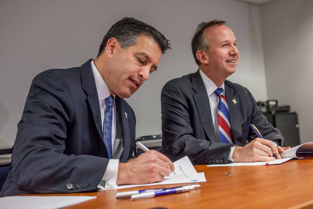 From left, Nevada Gov. Brian Sandoval and Delaware Governor Markell sign a multi-state Internet gaming agreement on Tuesday, Feb. 25, 2014 in Wilmington, Del.  (AP Photo/The Wilmington News-Journa ...