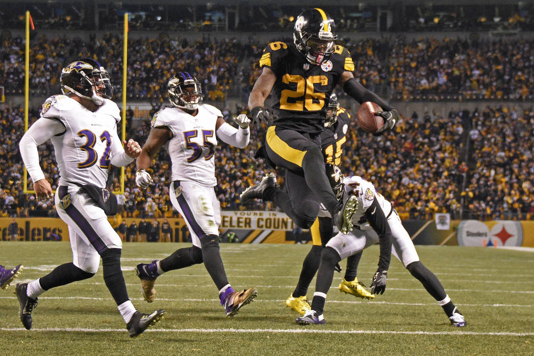 In this Dec. 25, 2016, file photo, Pittsburgh Steelers running back Le'Veon Bell (26) leaps into the end zone ahead of Baltimore Ravens strong safety Eric Weddle (32) for a touchdown during the se ...