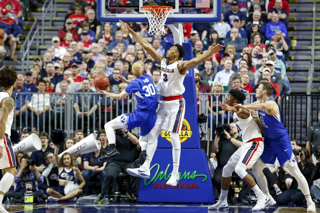 Brigham Young Cougars guard TJ Haws (30) attempts a shot as Gonzaga Bulldogs forward Johnathan Williams (3) goes in for the block during the West Coast Conference championship game at the Orleans  ...