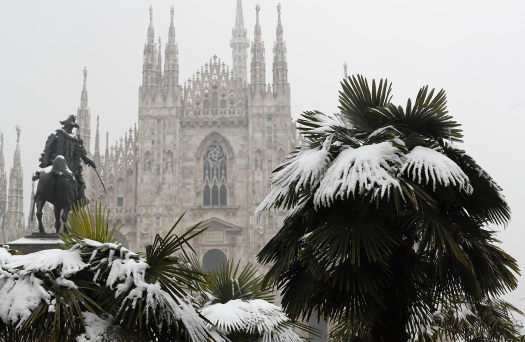 In this March 2, 2018, file photo, palm trees are dusted in snow after a snowfall in front of Milan's Gothic Cathedral, Italy. New U.S. weather data shows that the Arctic just finished its warmest ...
