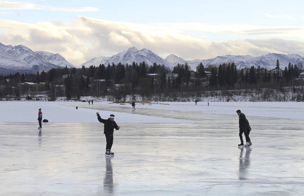 In this Jan. 2, 2018, file photo, ice skaters take advantage of unseasonable warm temperatures to ice skate outside at Westchester Lagoon in Anchorage, Alaska. New U.S. weather data shows that the ...