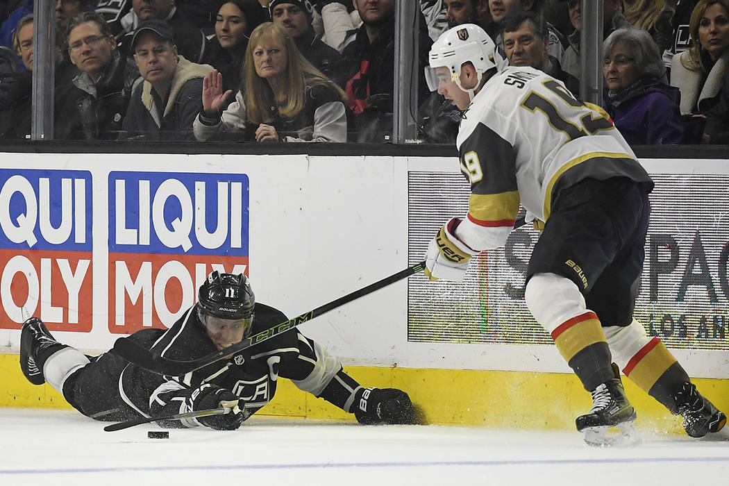 Los Angeles Kings center Anze Kopitar, left, of Slovenia, reaches for the puck along with Vegas Golden Knights right wing Reilly Smith during the second period of an NHL hockey game, Monday, Feb.  ...