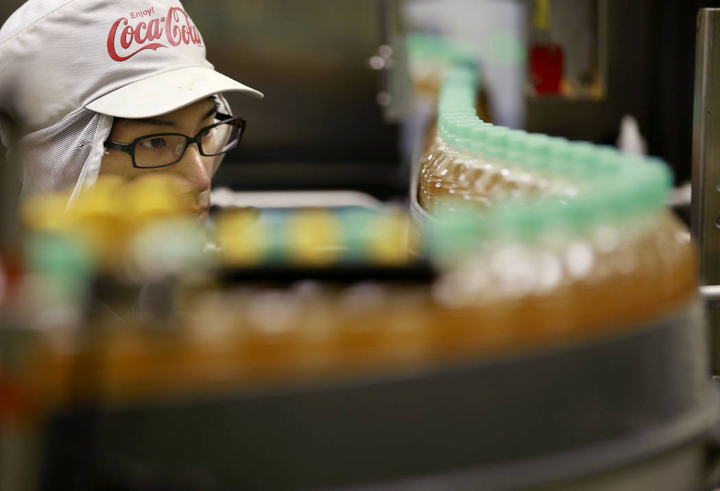 FILE- In this Nov. 17, 2016, file photo, a worker watches a product line at Coca-Cola Ebina plant in Ebina, Kanagawa Prefecture, near Tokyo. Coca-Cola may be getting into the booze business again  ...