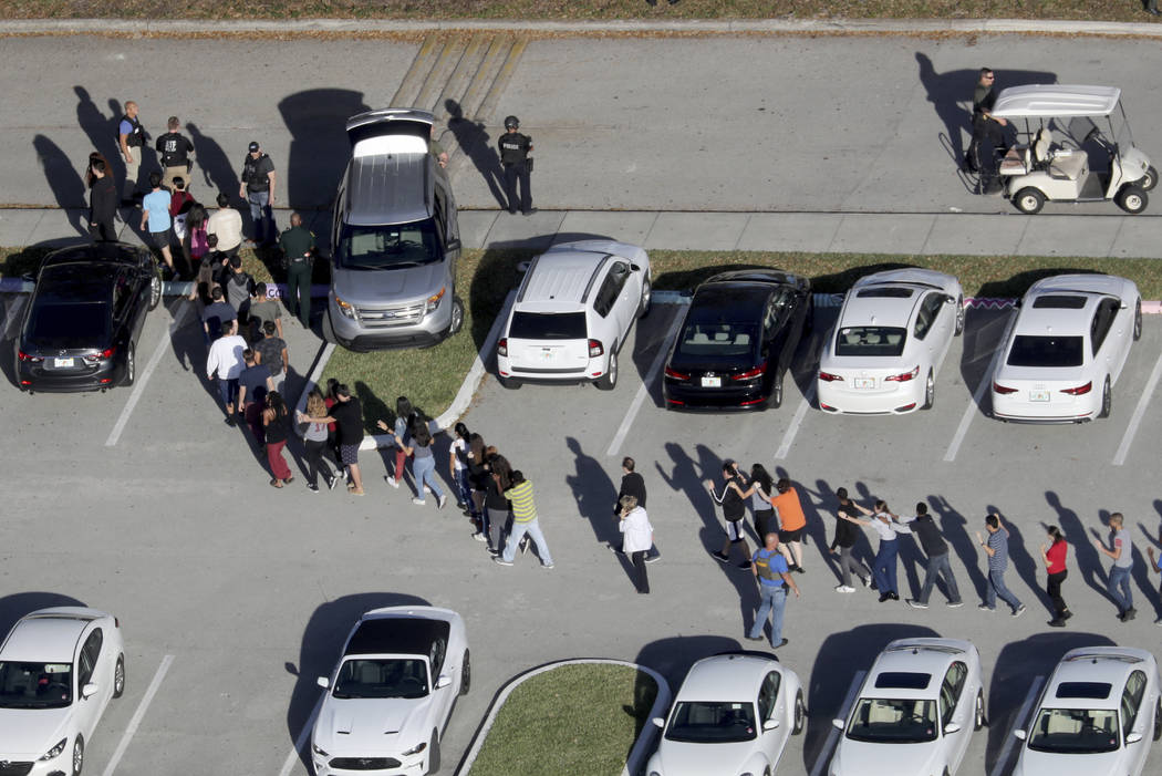 Students are evacuated by police from Marjory Stoneman Douglas High School in Parkland, Fla., after a shooter opened fire on the campus on Feb. 14, 2018. (Mike Stocker/South Florida Sun-Sentinel v ...