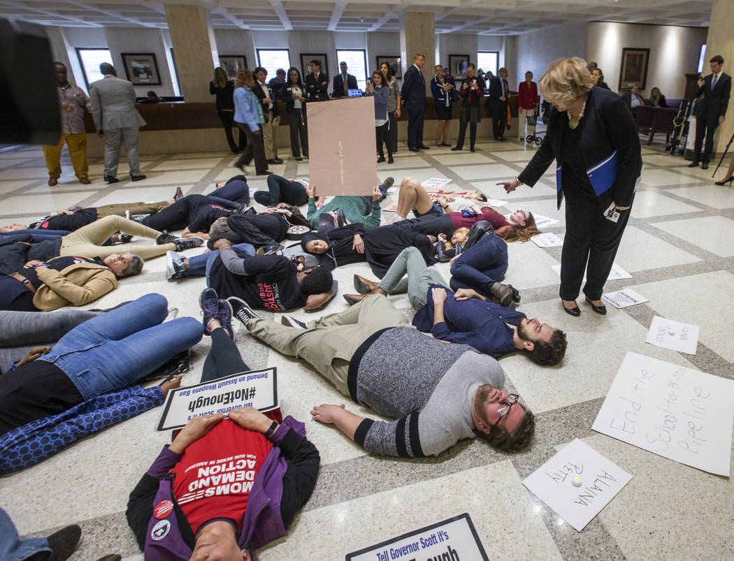 Florida Rep. Janet Cruz (D-Tampa) walks around a group of 20 college students and activists as they stage a die-in on the 4th floor rotunda between the House and Senate chambers while the House ta ...