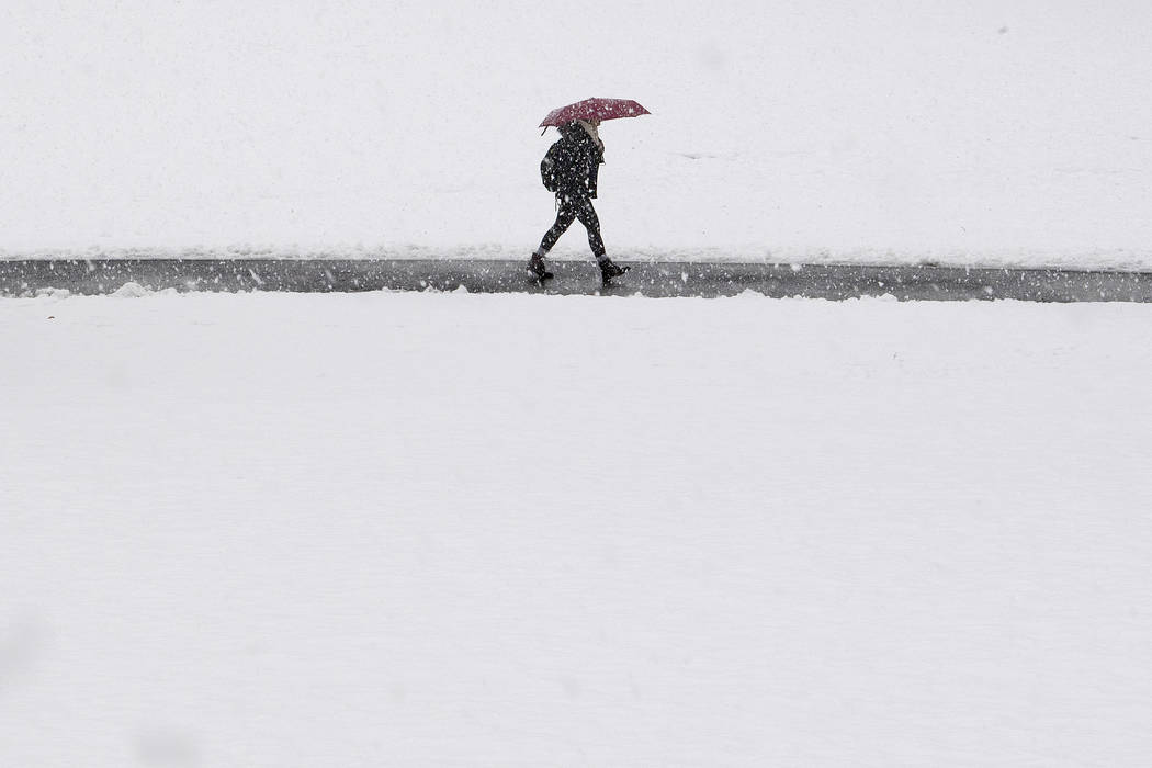 A pedestrian shields herself from the snow with and umbrella as she walks through campus grounds at Swarthmore College in Swarthmore, Pa., Wednesday, March 7, 2018. (Jose F. Moreno/The Philadelphi ...