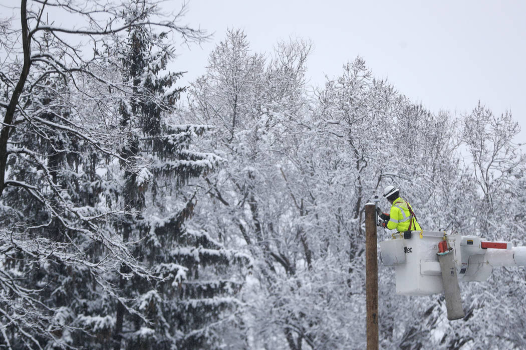 Phil Blair, a utility worker with PotomacEdison out of West Virginia, works on setting up a new power line as a crew works on restoring power along Molly Stark Drive ahead of a winter storm, Wedne ...
