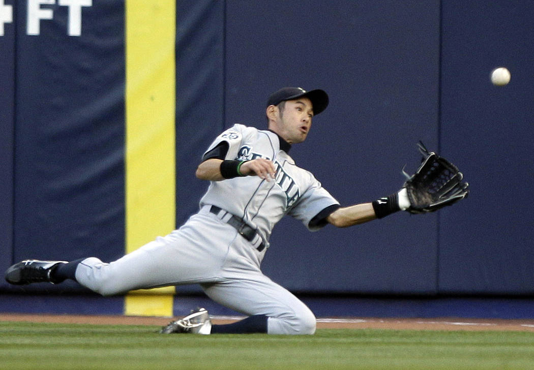 In this May 11, 2012, file photo, Seattle Mariners' Ichiro Suzuki, of Japan, dives to catch a ball hit by New York Yankees' Derek Jeter for an out during the first inning of a baseball game in New ...