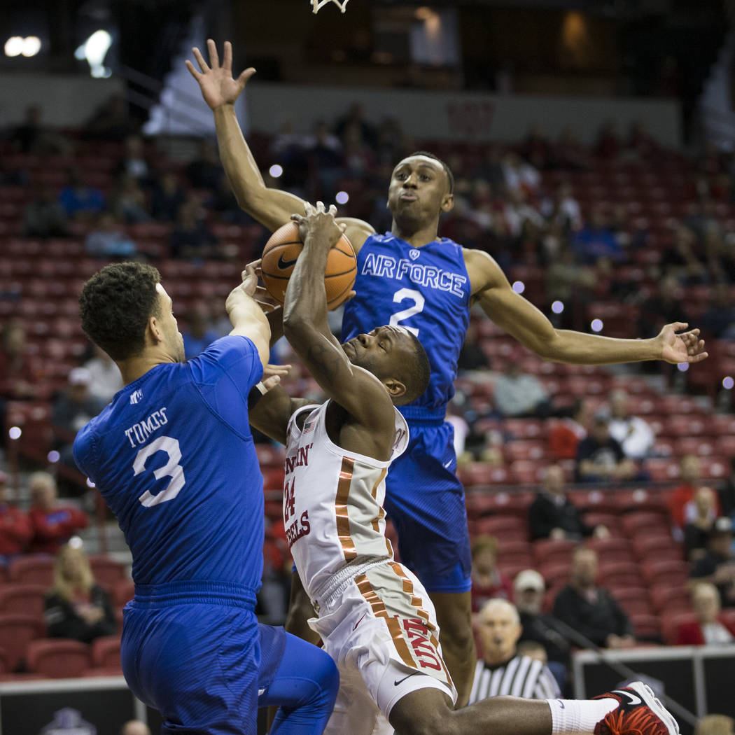 UNLV Rebels guard Jordan Johnson (24) takes a foul from Air Force Falcons guard Sid Tomes (3) as guard CJ Siples (2) leaps for a block in the first half of the Mountain West Conference men's baske ...