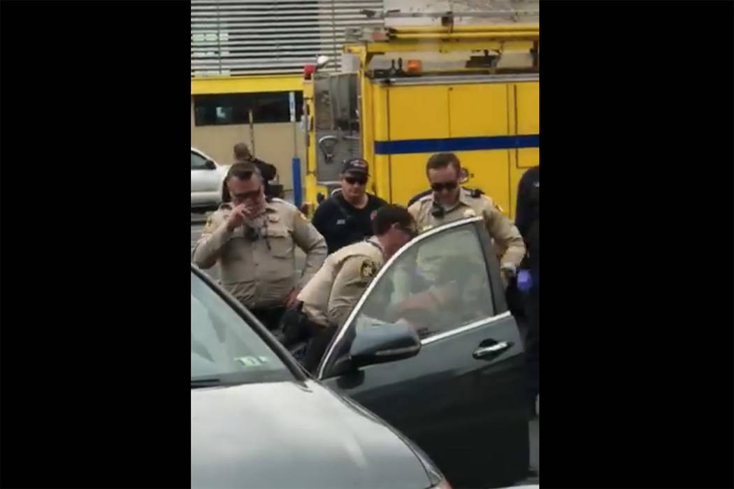 Images taken from a video by Steven Gibson of Las Vegas police arresting a man who was found unconscious in his car with a semi-automatic rifle and extra ammunition. (Steven Gibson/Facebook)
