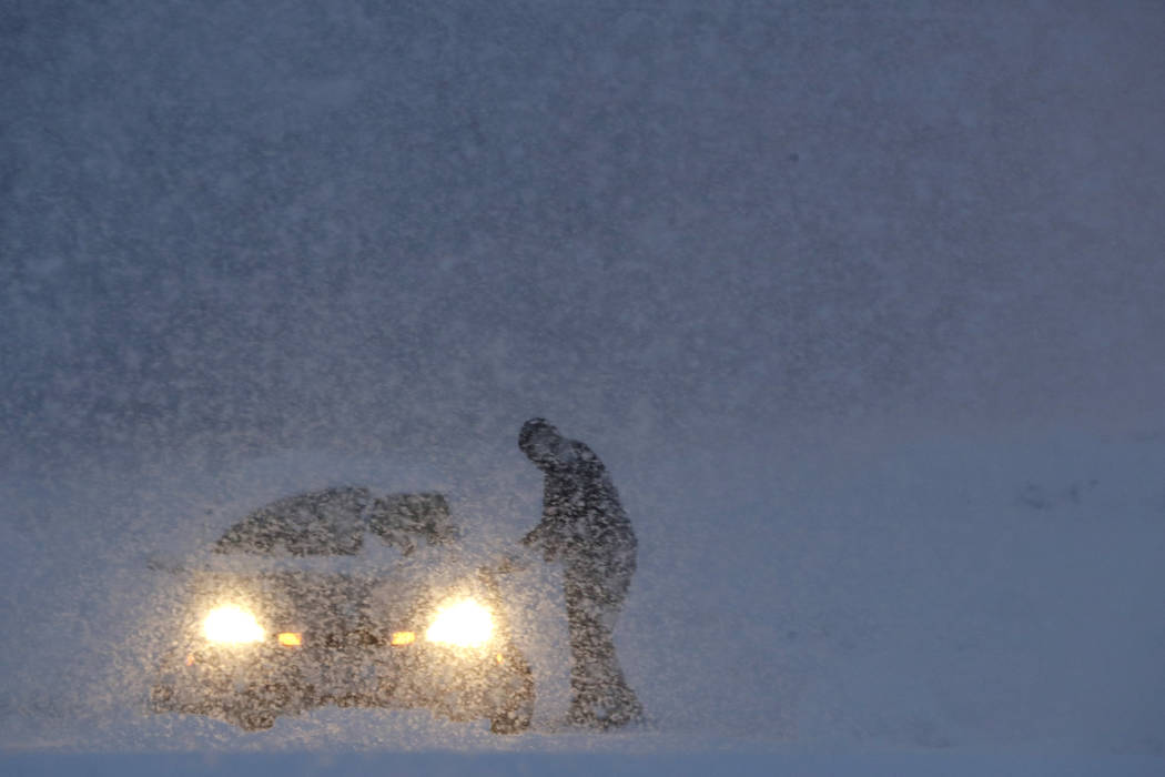 A man gets into a vehicle on a snowbank on the exit to a business along Route 23 during a snowstorm, Wednesday, March 7, 2018, in Wayne, N.J. (Julio Cortez/AP)