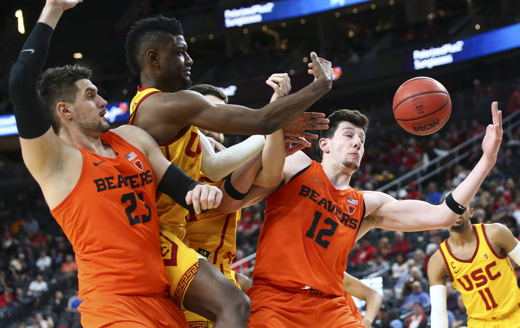 Oregon State Beavers forward Drew Eubanks (12) and center Gligorije Rakocevic (23) reach for a rebound against USC Trojans forward Chimezie Metu (4) during the Pac-12 basketball tournament at T-Mo ...