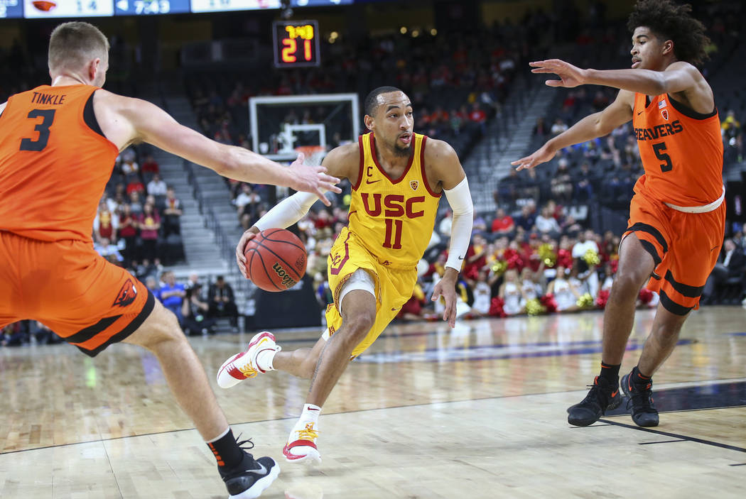 USC Trojans guard Jordan McLaughlin (11) drives to the basket between Oregon State Beavers forward Tres Tinkle (3) and guard Ethan Thompson (5) during the Pac-12 basketball tournament at T-Mobile  ...