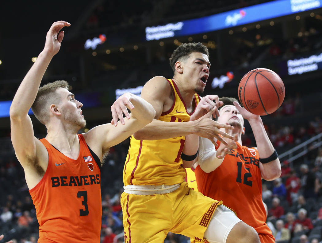 USC Trojans guard Jordan Usher (1) loses the ball he rebounded as Oregon State Beavers forwards Tres Tinkle (3) and Drew Eubanks (12) defend during the Pac-12 basketball tournament at T-Mobile Are ...
