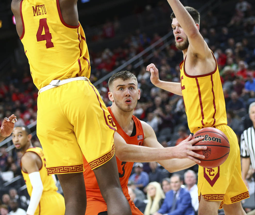 Oregon State Beavers forward Tres Tinkle (3) looks to pass as USC Trojans forwards Chimezie Metu (4) and Nick Rakocevic, right, defend during the Pac-12 basketball tournament at T-Mobile Arena in  ...