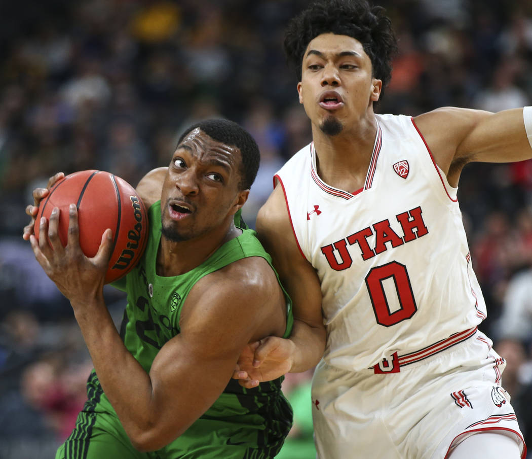 Oregon Ducks forward MiKyle McIntosh (22) eyes the basket as Utah Utes guard Sedrick Barefield (0) defends during the Pac-12 basketball tournament at T-Mobile Arena in Las Vegas on Thursday, March ...