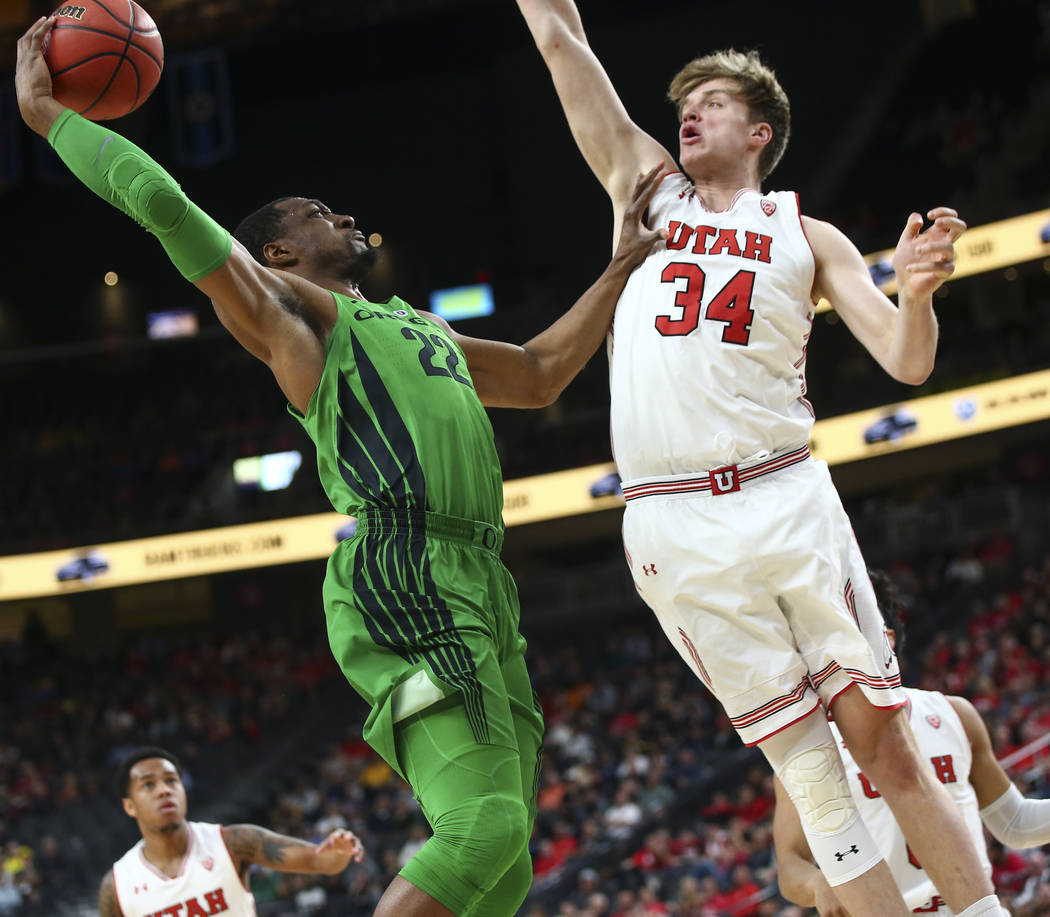 Oregon Ducks forward MiKyle McIntosh (22) goes to the basket against Utah Utes forward Jayce Johnson (34) during the Pac-12 basketball tournament at T-Mobile Arena in Las Vegas on Thursday, March  ...
