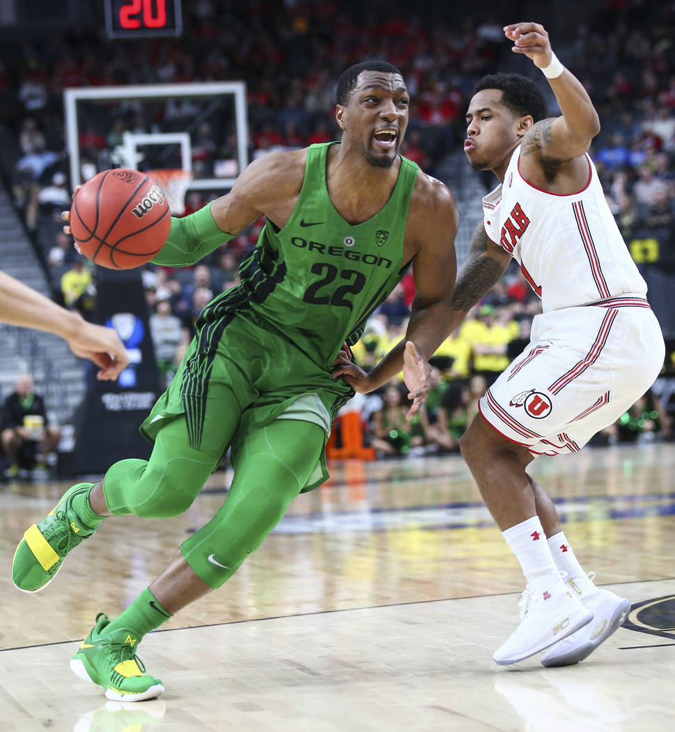 Oregon Ducks forward MiKyle McIntosh (22) drives as Utah Utes guard Justin Bibbins (1) defends during the Pac-12 basketball tournament at T-Mobile Arena in Las Vegas on Thursday, March 8, 2018. Ch ...