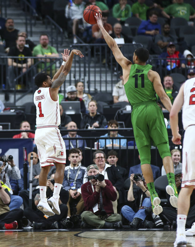 Oregon Ducks forward Keith Smith (11) blocks a shot from Utah Utes guard Justin Bibbins (1) during the Pac-12 basketball tournament at T-Mobile Arena in Las Vegas on Thursday, March 8, 2018. Chase ...
