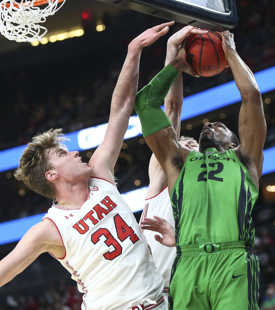 Oregon Ducks forward MiKyle McIntosh (22) gets fouled by Utah Utes forward Tyler Rawson (21) as forward Jayce Johnson (34) defends during the Pac-12 basketball tournament at T-Mobile Arena in Las  ...