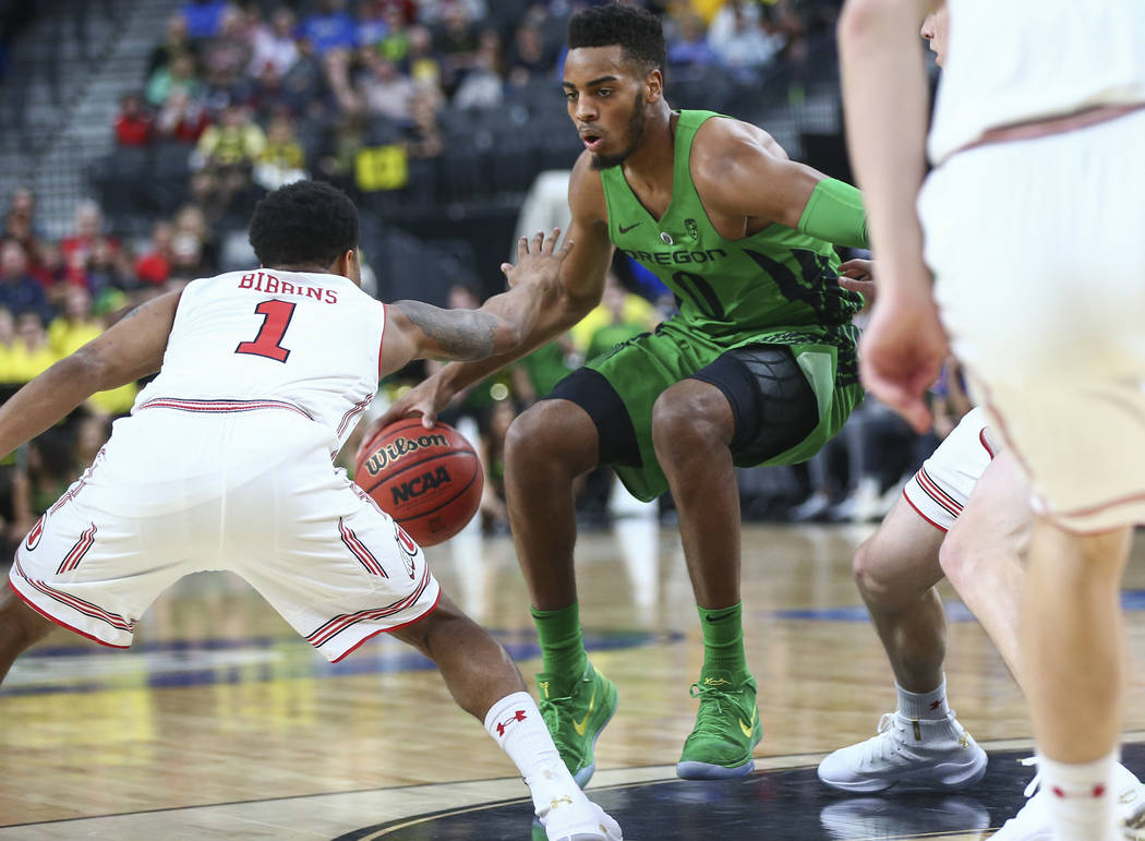 Oregon Ducks forward Troy Brown (0) drives the ball as Utah Utes guard Justin Bibbins (1) defends during the Pac-12 basketball tournament at T-Mobile Arena in Las Vegas on Thursday, March 8, 2018. ...