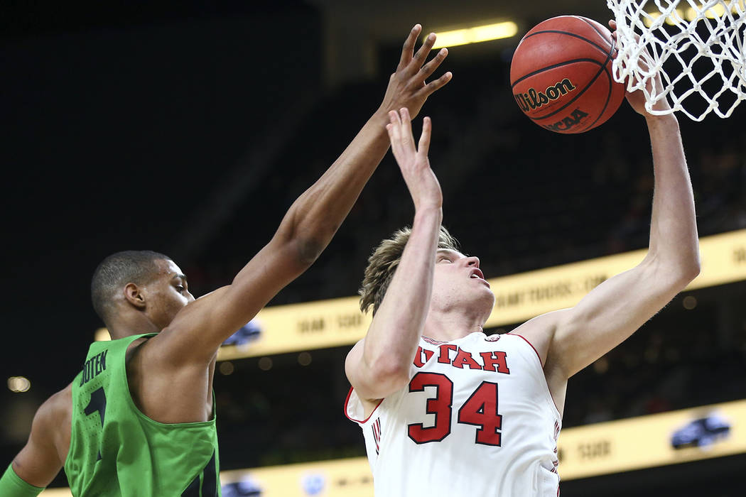 Utah Utes forward Jayce Johnson (34) gets a rebound over Oregon Ducks forward Kenny Wooten (1) during the Pac-12 basketball tournament at T-Mobile Arena in Las Vegas on Thursday, March 8, 2018. Ch ...