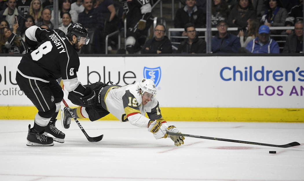 Vegas Golden Knights right wing Reilly Smith, right, dives for the puck while under pressure from Los Angeles Kings defenseman Drew Doughty during the third period of an NHL hockey game Thursday,  ...