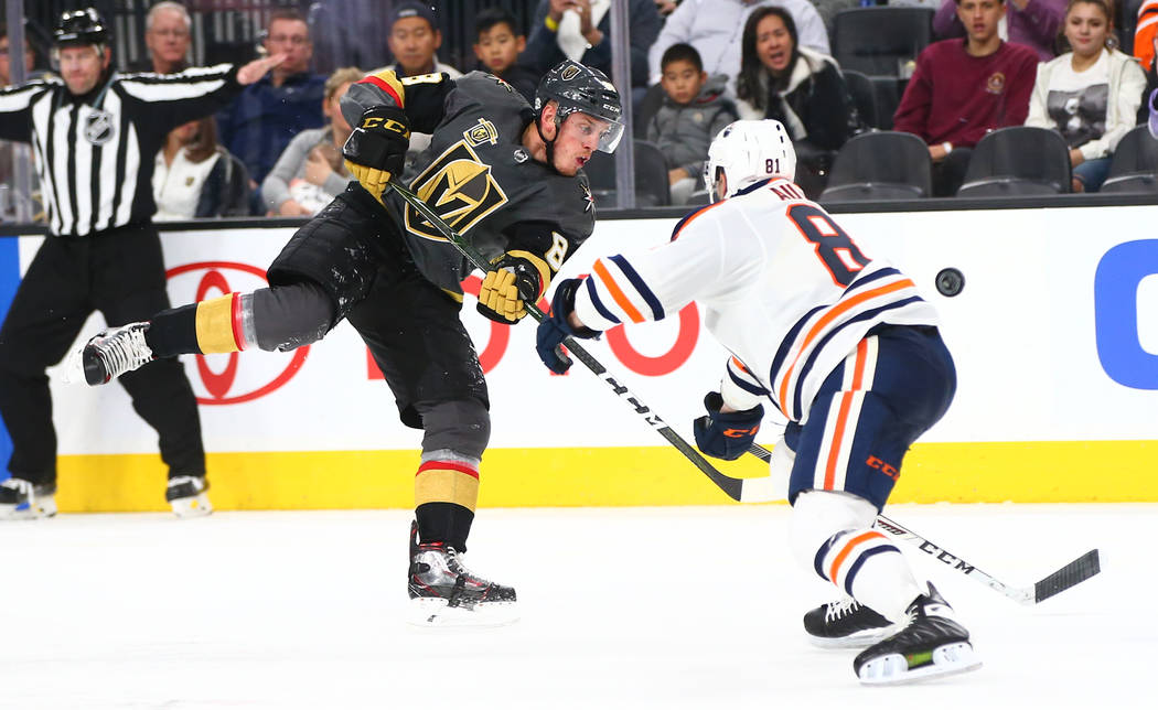 Golden Knights defenseman Nate Schmidt (88) sends the puck into the air against Edmonton Oilers defenseman Yohann Auvitu (81) during an NHL game at T-Mobile Arena in Las Vegas on Thursday, Feb. 15 ...