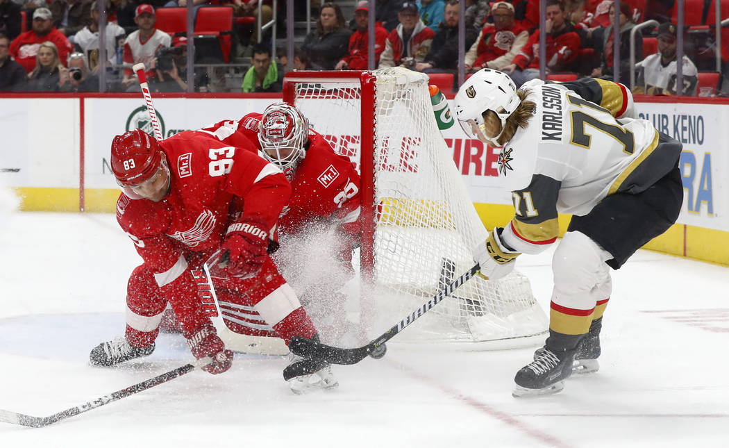 Detroit Red Wings defenseman Trevor Daley (83) deflects a shot by Vegas Golden Knights center William Karlsson (71) in front of goaltender Jimmy Howard during the first period of an NHL hockey gam ...