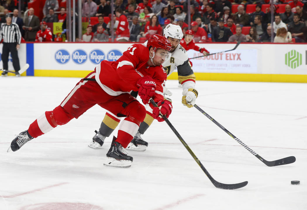 Detroit Red Wings center Dylan Larkin (71) shoots on Vegas Golden Knights defenseman Deryk Engelland (5) during the second period of an NHL hockey game Thursday, March 8, 2018, in Detroit. (AP Pho ...