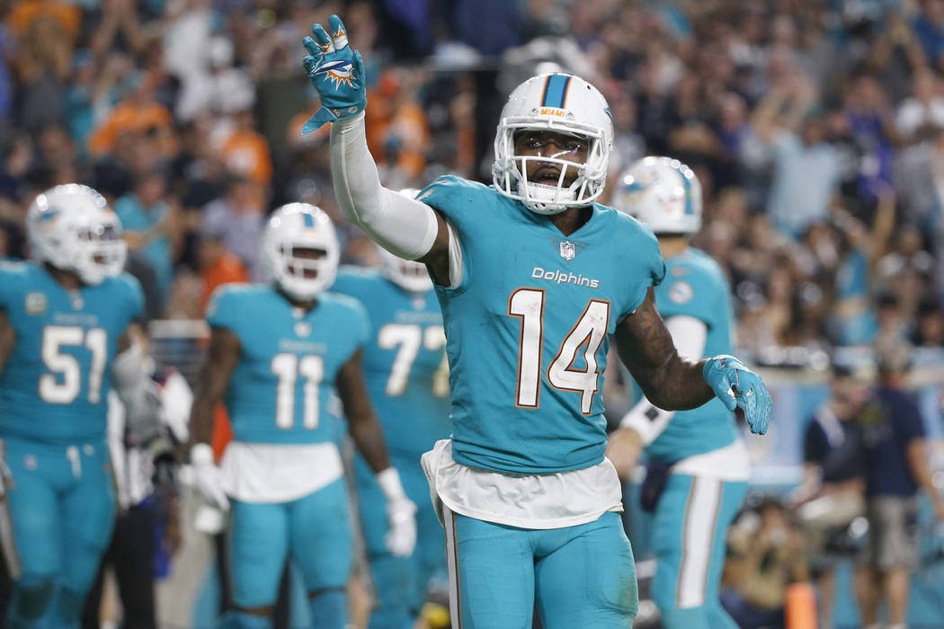 In this Sunday, Nov. 5, 2017 file photo, Miami Dolphins wide receiver Jarvis Landry (14) waves to fans after scoring a touchdown, during the second half of an NFL football game against the Oakland ...
