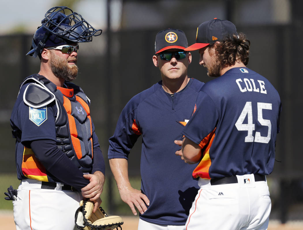 Houston Astros pitcher Gerrit Cole (45) talks with manager A.J. Hinch and catcher Brian McCann, left, after throwing a bullpen session during spring training baseball practice Thursday, Feb. 15, 2 ...