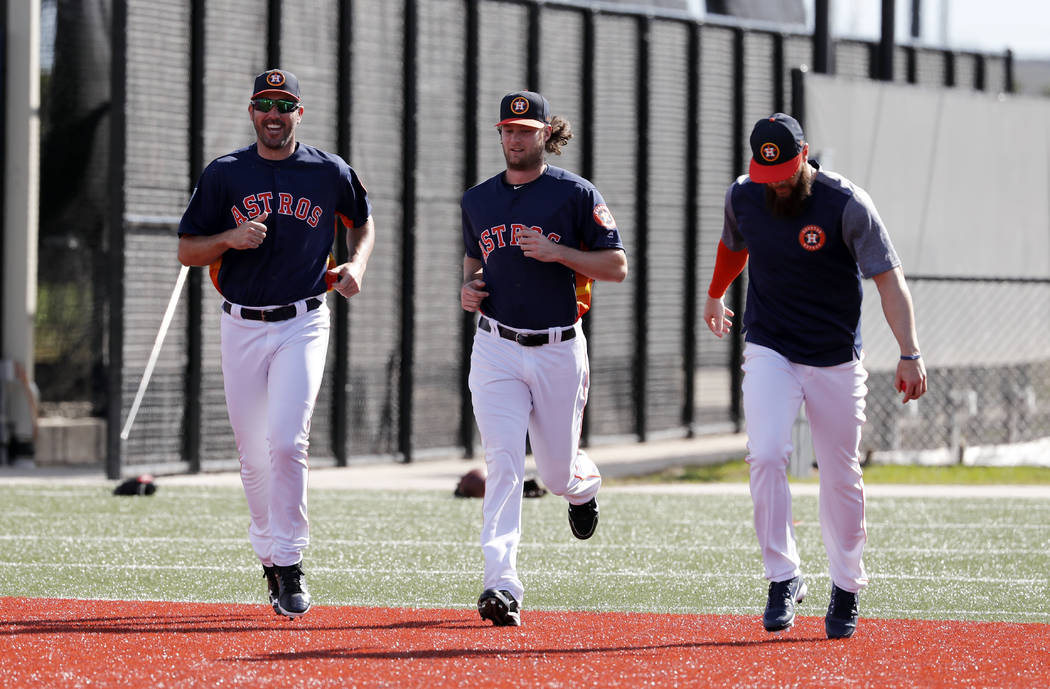 Houston Astros pitchers Justin Verlander, left, Gerrit Cole, center, and Dallas Keuchel jog as they warm up during spring training baseball practice Thursday, Feb. 15, 2018, in West Palm Beach, Fl ...