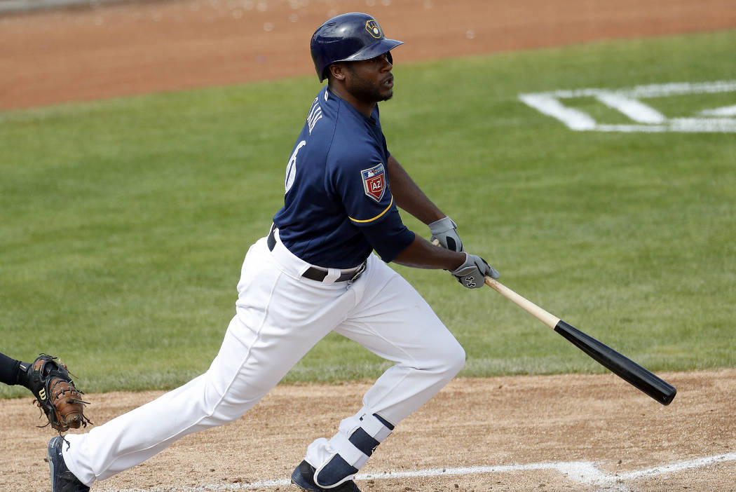 Milwaukee Brewers' Lorenzo Cain follows through on an RBI base hit against the Arizona Diamondbacks during the third inning of a spring training baseball game Thursday, March 8, 2018, in Phoenix.  ...