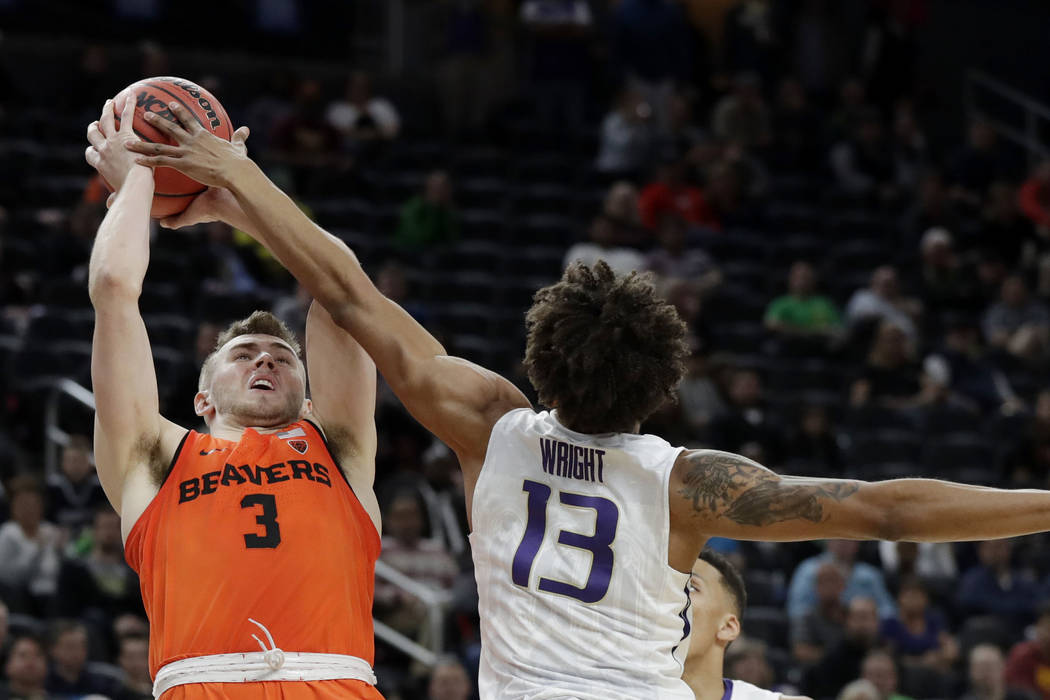 Washington's Hameir Wright, right, fouls Oregon State's Tres Tinkle during overtime in an NCAA college basketball game in the first round of the Pac-12 men's tournament Wednesday, March 7, 2018, i ...