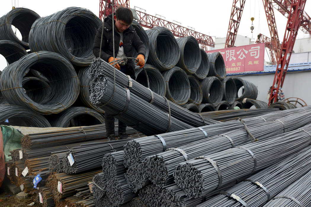 "A worker loads steel products onto a vehicle at a steel market in Fuyang in central China's Anhui province Friday, March 2, 2018. China has expressed ""grave concern"" about a U.S. trade p ..."